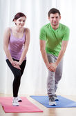 Woman and man stretching their legs — Stock Photo