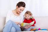 Mother reading book with child — Stock Photo