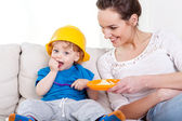 Boy eating meal and his mum — Stock Photo
