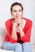 Woman sitting on a couch — Stock Photo