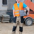 Smiling builder keeping toolbox — Stock Photo #47496323