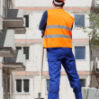 Builder with spade looking at construction — Stock Photo #47496667