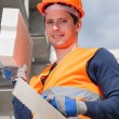 Builder with brick and spatula — Stock Photo #47535345