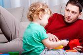 Pai olha para o seu filho a brincar — Fotografia Stock