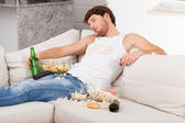 Wasted man surrounded by mess — Stockfoto
