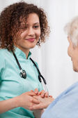 Young nurse holding a woman's hand older  — Stock Photo