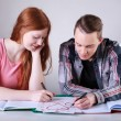 Teenage couple drawing hearts instead of learning — Stock Photo #47913431