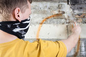 Hooligan painting graffiti — Stock Photo