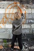 Hooligan painting graffiti on the building — Stock Photo