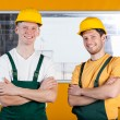 Workers in protective workwear standing with arms crossed — Stock Photo #47980415