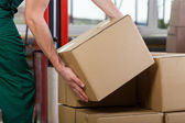 Hands of warehouse worker lifting box — Stock Photo