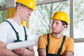 Two men in overalls and hardhat during work — Stock Photo
