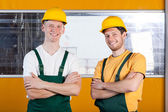 Workers in protective workwear standing with arms crossed — Stock Photo