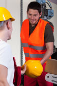 Factory worker giving his collaborator hardhat — Stock Photo