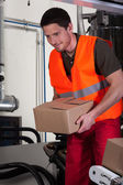 Blue-collar worker holding box — Stockfoto