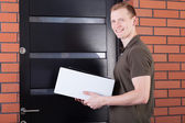 Mail carrier with a package — Stock Photo