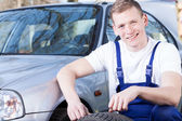 Glad mechanic changing a tire — Stock Photo