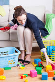 Lady cleaning up toys — Stock Photo