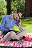 Woman making notes in the park — Stock Photo
