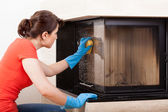 Housekeeper cleaning  fireplace — Stock Photo