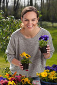 Woman holding pots with flowers — Stockfoto