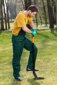 Man in dungarees digging in garden — Stock Photo