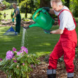 Man watering the flowers when his wife cleans lawn — Stock Photo #48703511