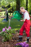 Man watering the flowers when his wife cleans lawn — Stock Photo