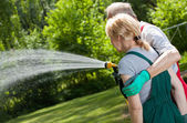 Married couple watering the lawn  — Stock Photo