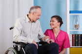 Nurse smiles to sitting patient — Stock Photo