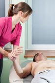 Therapist stretching man's arm — Stock Photo