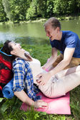 Boy tickling girl by the lake — Stock Photo