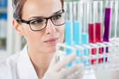 Woman looking at test tubes — Foto de Stock