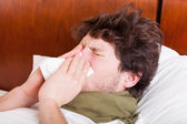 Young sick man blowing nose — Photo
