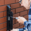 Senior man repairing gate lock — Stock Photo #49353217