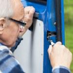 Close-up of a man repairing car door — Stock Photo #49353637
