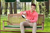 Asian man drinking tea in garden — Stock Photo