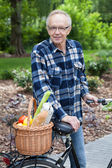 Male cyclist with wicker basket full of groceries — Stock Photo