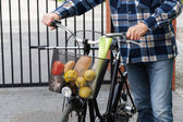 Man and bicycle basket full of groceries — Stock Photo