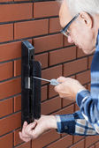 Senior man repairing gate lock — Stock Photo