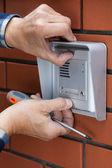 Male hands repairing intercom — Stock Photo