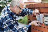Handyman fixing intercom — Stock Photo