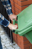 Male hands pushing a wheeled dumpster — Stock Photo