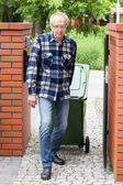 Elderly man pulling a wheeled dumpster — Stock Photo