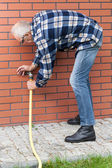 Man repairing leaky garden hose spigot — Stock Photo