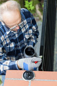 Gray-haired man painting modern metal gate — Stock Photo