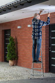 Man standing on the ladder and tightening ventilation grille — Stock Photo