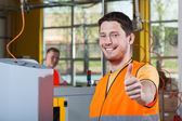 Machine operator showing thumbs up sign — Stock Photo