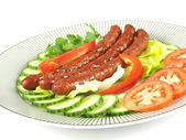 Fried sausages with decoration on plate — Stock Photo