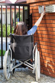 Woman on wheelchair dialing intercom — Stock Photo